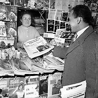"""Janvier 1957. Vue d'Abdelhamid Bouchouk, joueur du Toulouse Football Club, distribuant le journal """"Toulouse Football"""" à une vendeuse de journaux installée dans un kiosque"""
