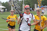 The University of Virginia women's lacrosse player Liz Downs(7) moves past Towson's Jess Dunn(22) and Jacie Kendall(4) during the first game since the tragic death of Virginia player Yeardley Love Sunday May 16, 2010 at Klockner Stadium in Charlottesville, Va. The Cavaliers rallied in the last four minutes to beat Towson 14-12  and reach the quarter finals of the NCAA tournament. Love's body was found May 3, and Virginia men's lacrosse player George Huguely is charged with murder. Photo/Andrew Shurtleff...