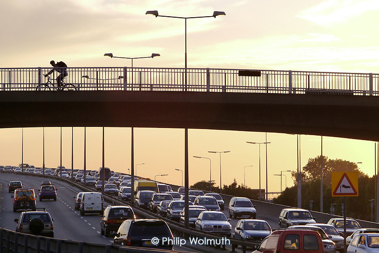 A cyclist crosses a bridge above rush hour traffic on the North Circular Road in West London