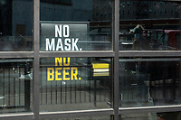 """A sign in the window of Cheeky Monkey Brewing Company reads """"No mask, no beer,"""" in Boston, Massachusetts, on Wed., Jan. 6, 2021."""