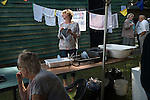 Ebernoe Horn Fair West Sussex UK.  Tea tent lady washing and drying dishes. 2015.