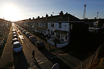 Fans walking to the game silhouetted by low winter sunlight. Like many late victorian football grounds, Blundell Park is surrounded by terraced houses. Grimsby Town v Lincoln City, Football Conference, 28th December 2014.