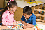 Education preschool 4 year olds boy and girl looking at and talking about picture book pointing a illustration language development horizontal