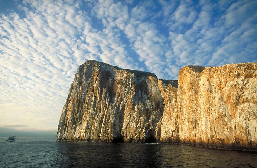 Tourist boat cruises along the steep rock slope of Kicker Rock near San Cristobal Island, cloud formations, clouds, cliffs. Kicker Rock (Sleeping Lion Rock) Galapagos Islands Ecuador Pacific Ocean, 650 miles west of South America.