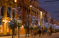 Beautiful night time exposure of Puerta de Jerez square and colorful buildings on street with excitement in Seville Spain downtown