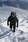 Winter hiker on the summit of South Twin Mountain in the White Mountains, New Hampshire during the winter months. Windy conditions cause snow to blow around. The Appalachian Trail crosses the summit of South Twin Mountain.