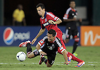 WASHINGTON, DC. - AUGUST 22, 2012:  Marcelo Saragosa (11) of DC United is tripped by  Marco Pappa (16) of the Chicago Fire during an MLS match at RFK Stadium, in Washington DC,  on August 22. United won 4-2.