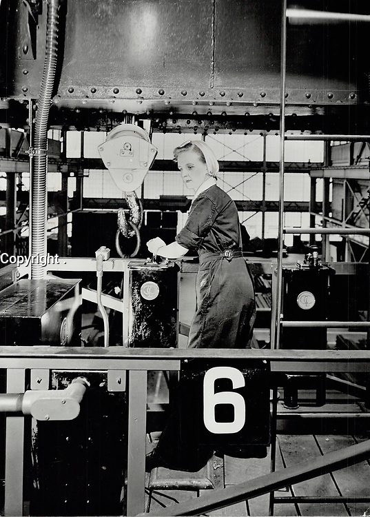 A girl crane operator; Mrs. Blanche Millette; lifts a ten-ton load as easily as she would operate a sewing machine. She is one of thousands praying women have a definite place in ward plants<br /> <br /> PHOTO : Toronto Star Archives - AQP