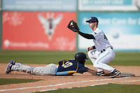 Will Bartlett (44) of the Lynchburg Hillcats receives a pick off attempt as Edmond Americaan (20) of the Myrtle Beach Pelicans dives back towards first base at Bank of the James Stadium on May 23, 2021 in Lynchburg, Virginia. (Brian Westerholt/Four Seam Images)