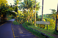 Entrance sign near a road for the Hawaii tropical botanical gardens