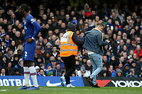 A pitch invader who is being escorted off the pitch by a Chelsea steward casually gets out his mobile phone during Chelsea vs Everton, Premier League Football at Stamford Bridge on 8th March 2020