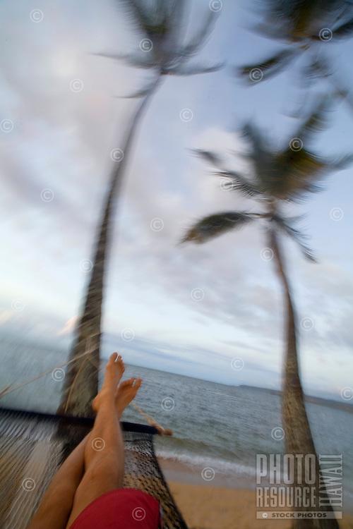 Man swinging in hammok under palm trees at sunset