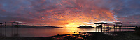 Panoramic photograph of dawn at Clear Lake, viewed from the shoreline at North Lakeport, Lake County, California. The volcano Mount Konocti is in the background. Piers appear unusually high because of an extensive drought.