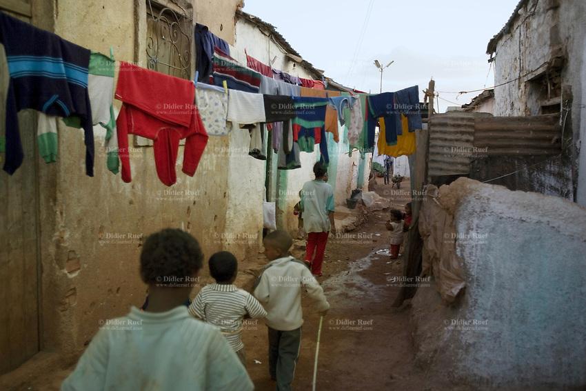 Eritrea. Maekel province. Asmara. Children walk on a dirt path in a slum area. Clean clothes are drying on a rope. © 2006 Didier Ruef