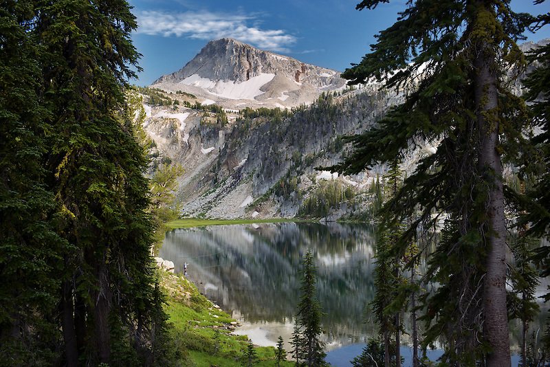 Fly fisherman and reflection in Mirror Lake with Eagle Cap Mountain. Eagle Cap Wilderness, Oregon