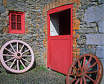 County Clare, Ireland: Stone walls and cobbled stable yard with colorfully painted wagon wheels and stable door at Bunratty House,  Bunratty Folk Park