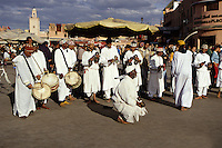 Marrakesh, Morocco - Gnaoua Musicians and Dancers, Place Jemaa El-Fna.  Cowrie Shell Decorations on Caps. The metal castanets are called qarqaba, the drums tbol.