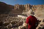 A male tourist wearing a red shirt, hat, and jeans, visits the dazzling Temple of Hatshepsut at Deir al-Bahri on the West Bank of the Nile Valley in Luxor, Egypt.