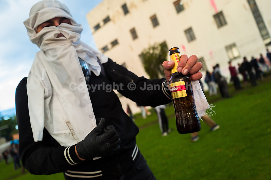 A radical student of the Universidad Nacional de Colombia shows a Molotov cocktail bottle during in a protest march against government's policies and corruption within the public educational system in Bogotá, Colombia, 24 October 2019.