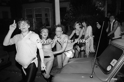 """A Hot Chocolate themed Christmas party named after the 1970s and 1980s pop group of the time. """"You Sexy Thing"""", was one of their numerous hits. Suburban middle class fancy dress party. Wimbledon SW19. England. 1983.<br /> Conga line dance in the street."""