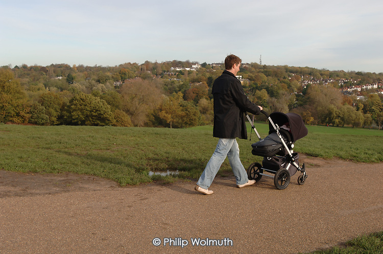 A father pushes a buggy over Parliament Hill,  Hampstead Heath, London.