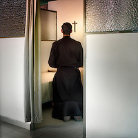 A priest prays in his cell by his bed in front of a crucifix at the Legionaries of Christ seminary in Salamanca. The Legion of Christ is a conservative Roman Catholic congregation whose members take vows of chastity, obedience and poverty.