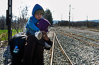 Pictured: A young mother carries her child on her shoulders and about to cross railway tracks to get to Idomeni Wednesday 02 March 2016<br /> Re: More migrants have been arriving at the Greek FYRO Macedonian border of Idomeni, Greece.