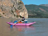 Charles Buckely rows a cataraft past a fish wheel along the Alaska's Yukon River.