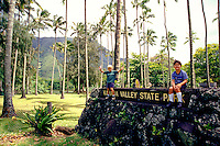 Two children sit on the entrance sign to Kahana Valley State park on Oahu's north shore