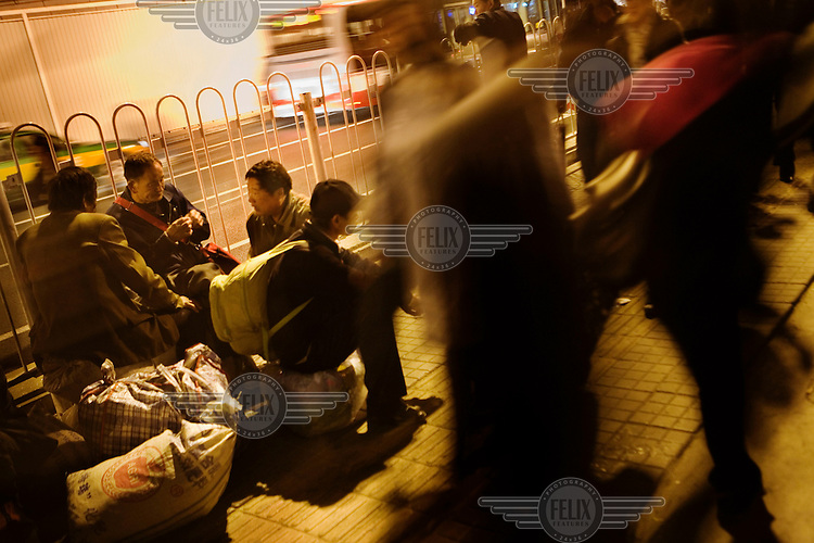 Migrant workers, who have just arrived in the city with heavy luggage, take a rest on the pavement during rush hour.