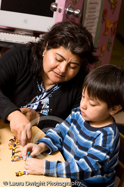 Education Preschool 3-4 year olds female teacher working with boy playing with small plastic figures vertical