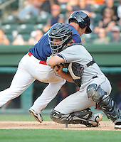 Catcher Justin Garneau (15) of the Asheville Tourists, Class A affiliate of the Colorado Rockies, makes the tag for an out in a game against the Greenville Drive on May 1, 2011, at Fluor Field at the West End in Greenville, S.C. Photo by Tom Priddy / Four Seam Images