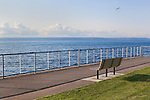 An empty bench in a waterfront park on Puget Sound under partly cloudy skies at Des Moines Marina, city of Des Moines, Washington, USA.