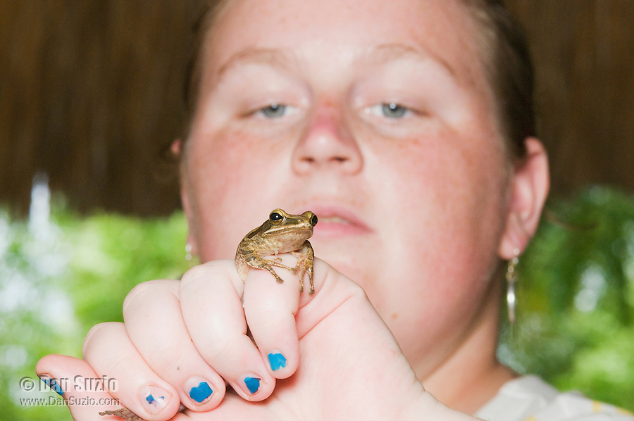 American biology student Mary Weil poses with a striped treefrog, Polypedates cf. leucomystax, in Timor-Leste (East Timor). (specimen # 547)