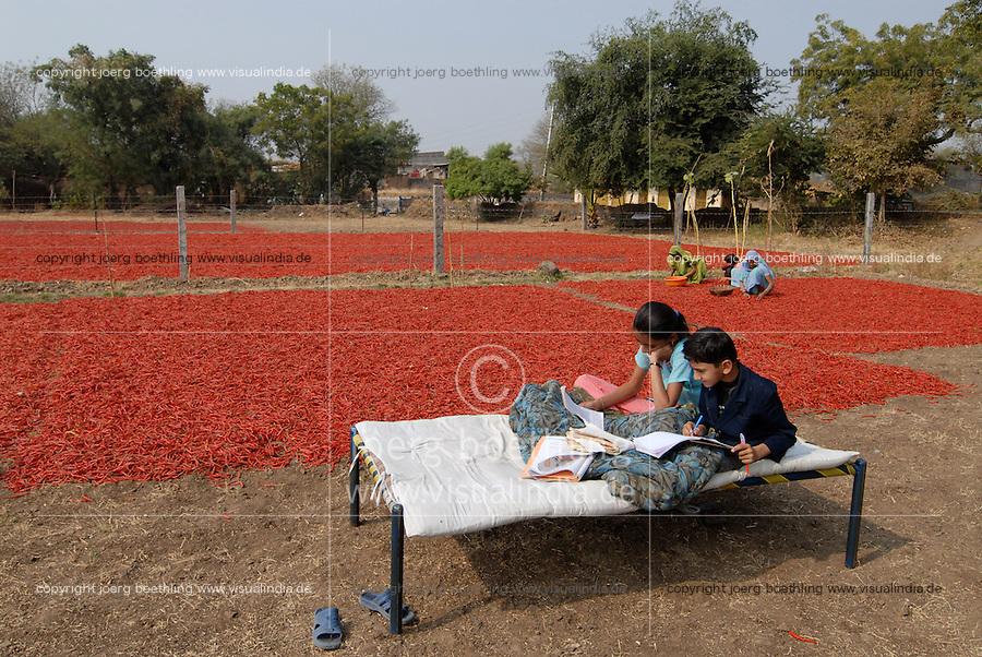 INDIA Madhya Pradesh, children on traditional bed charpoy, doing home works for school, red chilies dry in sun at farm / INDIEN Madhya Pradesh, Kinder sitzen auf einem Bett und machen Hausaufgaben fuer die Schule, rote Chili Schoten in der Sonne