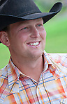 Portrait of a smiling young man in a cowboy hat chewing on blade of grass