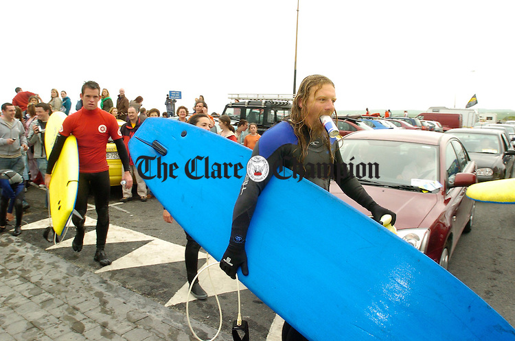 Surfers return ashore after taking part  in the Lahinch Surfschool Crew's Surfing World Record Festival at Lahinch beach. Photograph by John Kelly.