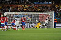 Ghana forward Asamoah Gyan converts a penalty against Serbian goalkeeper Vladimir Stojkovic. Ghana defeated Serbia, 1-0, June 13th, in the opening match of Group D of the 2010 FIFA World Cup.