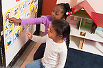 Education preschool 3-4 year olds two girls and a boy looking at illustrations of the daily schedule and talking