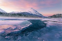 Reflected light on the icy banks of a frozen river lead to King's Peak in the distance, complemented by a spectrum of pastel hues in the soft sunrise light.