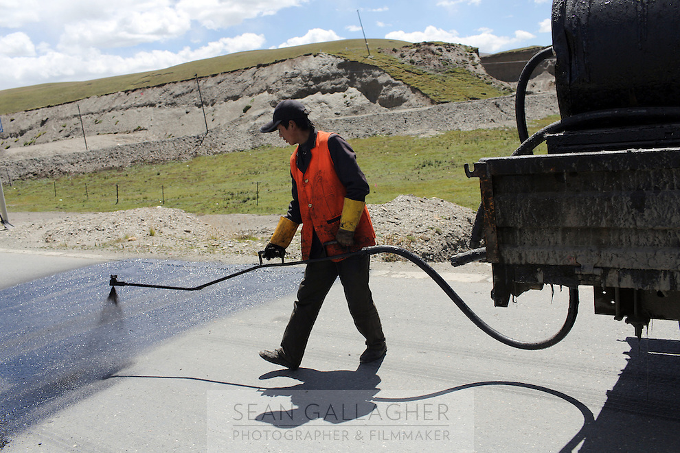 A Chinese highway worker conducts maintenance on a road on the Tibetan Plateau, in western China.