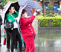 Nanjing, Jiangsu, China.  Woman with Breathing Mask Taking a Photo with her Cell Phone.