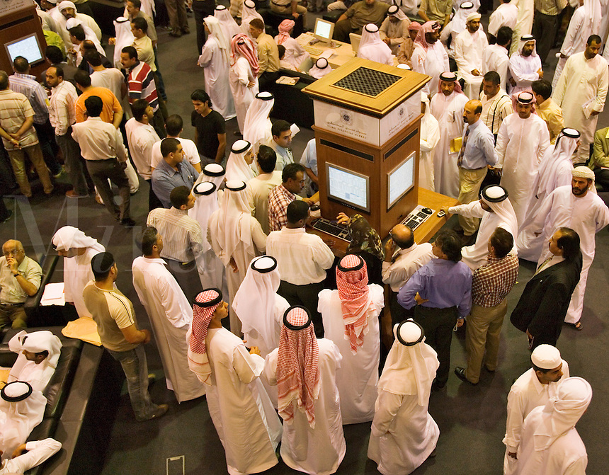 Investors at the Dubai Financial Market, the local Stock Exchange,  gather round the display showing the latest prices.  Dubai. United Arab Emirates.
