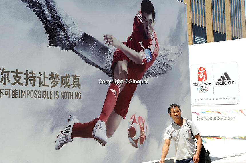 A man walks past Adidas billboard for Beijing Olympics..