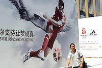 A man walks past Adidas billboard for Beijing Olympics..