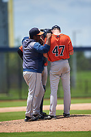 GCL Astros pitching coach Jose Rada talks with pitcher Kevin Dickey (47) and catcher Tyler Krabbe (56) during a Gulf Coast League game against the GCL Nationals on August 9, 2019 at FITTEAM Ballpark of the Palm Beaches training complex in Palm Beach, Florida.  GCL Nationals defeated the GCL Astros 8-2.  (Mike Janes/Four Seam Images)