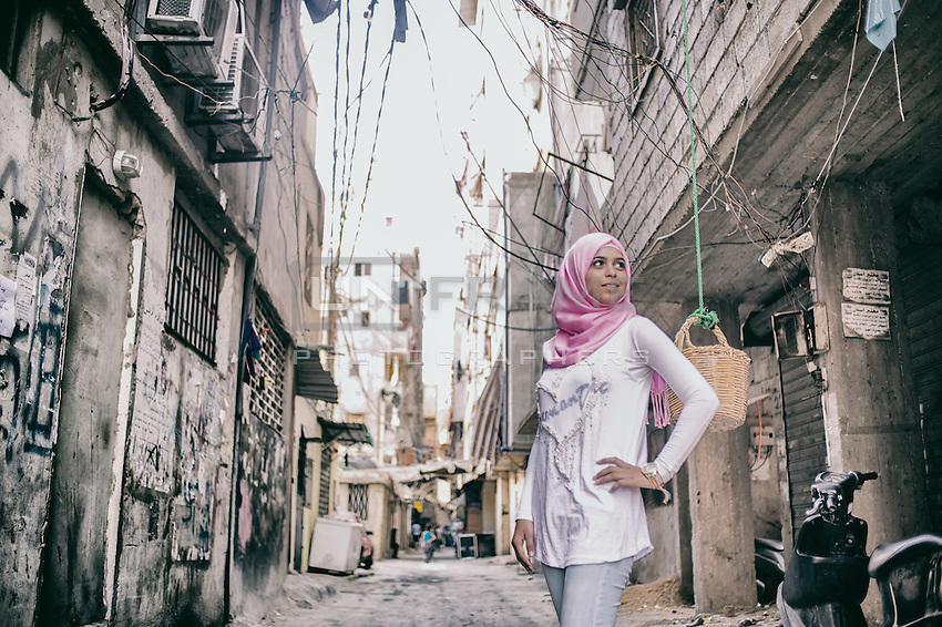 Palesinian teenager posing for the picture in the street of Shatila camp. She studies law but knows that in Lebanon she won't be allowed to get a skilled job. She will plan on travelling to other country recognising Palestinians rights. Shatila, Beirut, Lebanon 2015