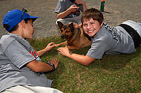 Batavia Muckdogs youth baseball clinic participants play with Georgia, groundskeeper Don Rock's dog, on August 30, 2017 at Dwyer Stadium in Batavia, New York.  (Mike Janes/Four Seam Images)