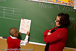 K-8 Parochial School Bronx New York Kindergarten female teacher standing at blackboard male student solving problem in math worksheet taped to board horizontal