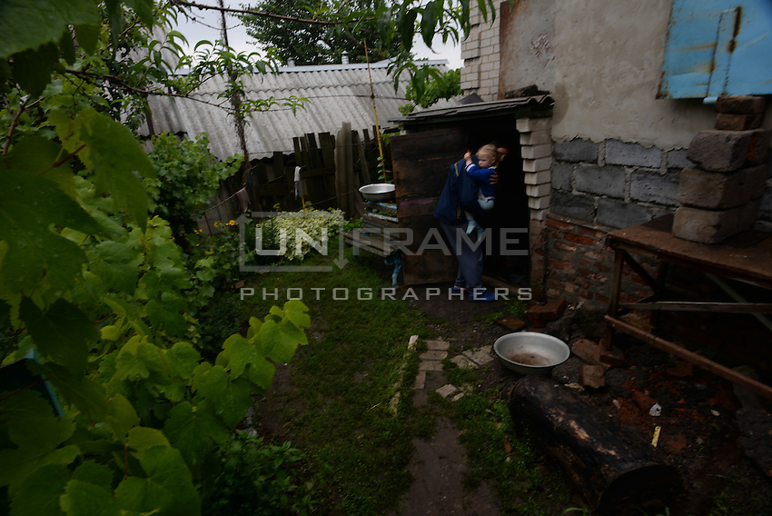 Slovyansk. A father brings his child into the basement turned into shelter from shelling.